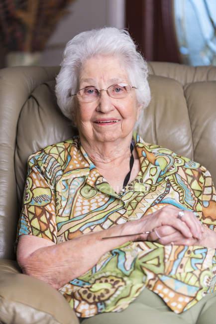 Возрасте женщина, сидя в кресле — стоковое фото