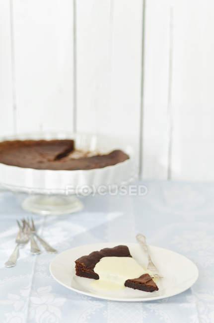 Pedazo de tarta de chocolate con crema pastelera en placa - foto de stock
