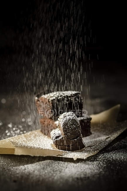 Sprinkling Brownies on baking paper with icing sugar — Stock Photo
