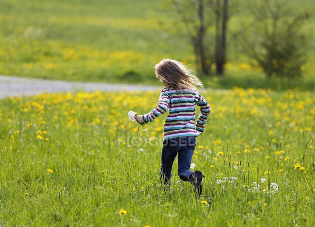 Fille courir dans prairie et tenant des fleurs — Photo de stock