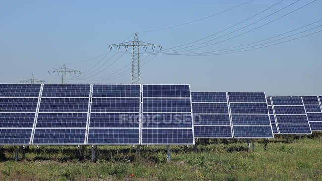 Germany, Bavaria, Solar panels with power pole in background — Stock Photo