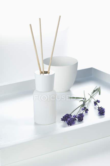 Diffuseur de parfum avec bâtons d'arôme et fleur de lavande sur fond blanc — Photo de stock
