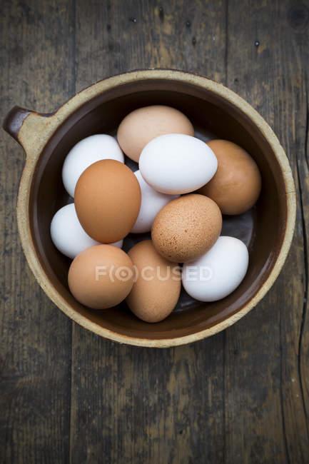 Яйца в миску на деревянный стол — стоковое фото