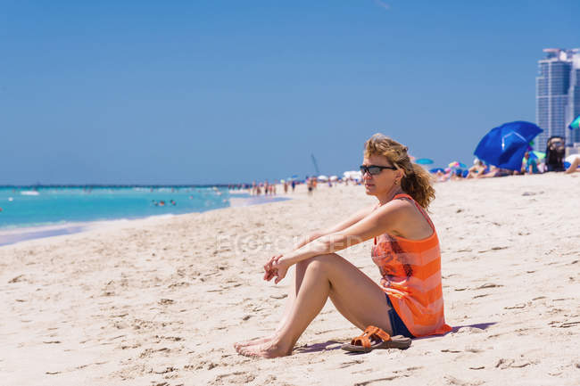 USA, Florida, Miami Beach, Mature woman sitting on beach — Stock Photo