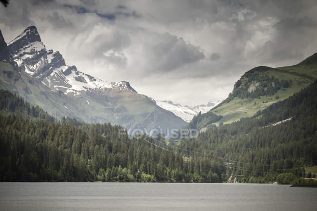 Швейцария, швейцарские Альпы на Роди-Фиессо с озером против вершин над водой — стоковое фото