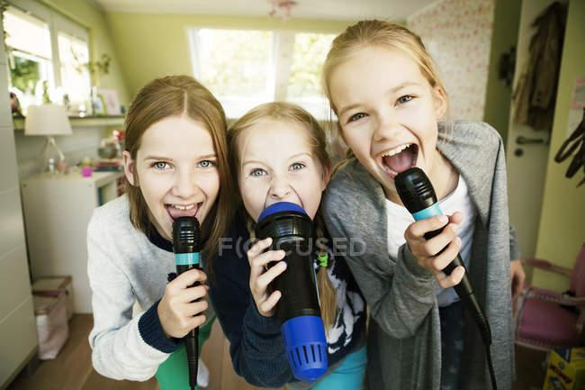 Tre ragazze che cantano con microfoni a casa — Foto stock
