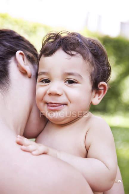 Mère câlinant son petit garçon, souriant — Photo de stock