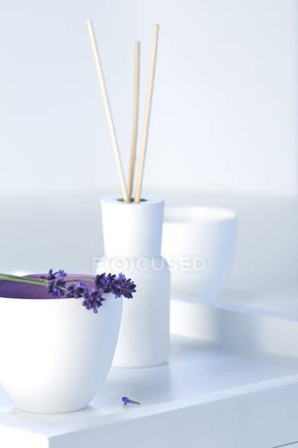 Fleurs de lavande et bâtonnets d'arôme en bouteille sur plateau blanc — Photo de stock