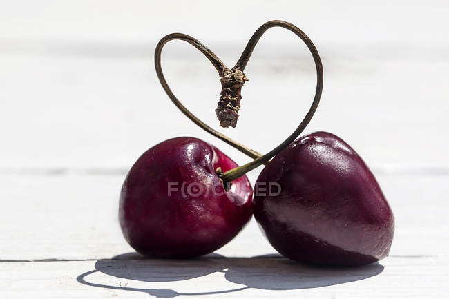 Close-up de hastes de cerejas formando coração forma na superfície de madeira branca — Fotografia de Stock