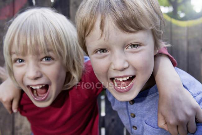 Мальчики играют на детской площадке, улыбаются в камеру — стоковое фото