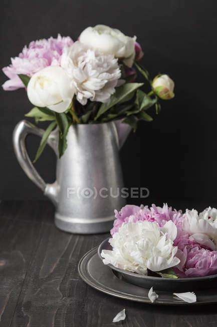 Frisch geschnittene weiße und rosa Pfingstrosen auf dunklem Holztisch — Stockfoto