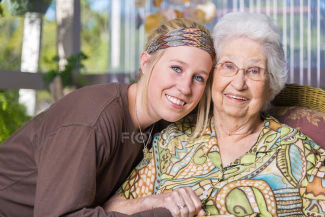 Возрасте женщина и ее правнучка бок о бок — стоковое фото