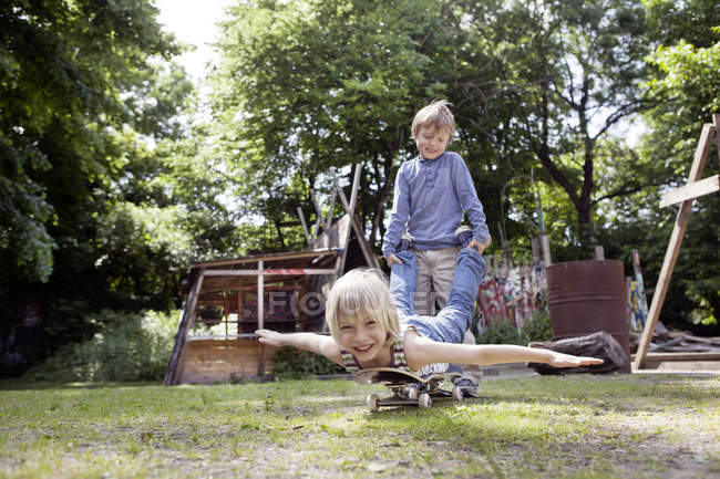Boys playing with skateboard at playground, smiling at camera — Stock Photo