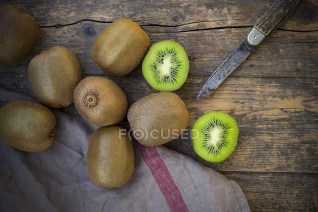 Frische ganze und halbierte Kiwis mit Messer auf dunklem Holz — Stockfoto