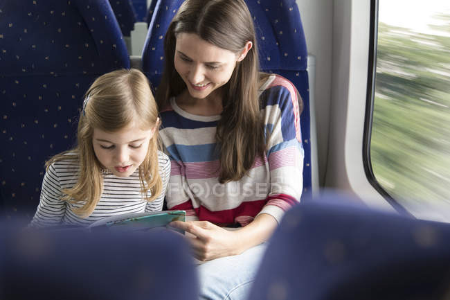 Mother and daughter reading book in a train — Stock Photo
