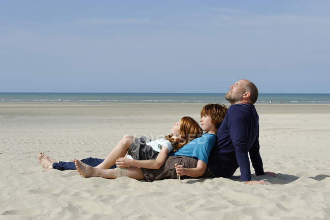Father with son and daughter relaxing on sandy beach — Stock Photo
