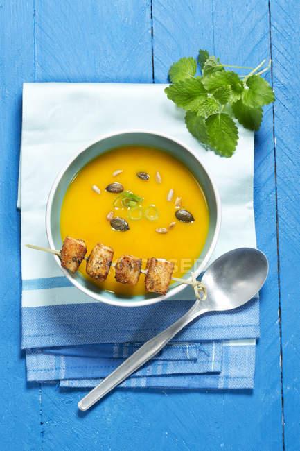 Вид зверху пюре гарбуз суп в миску з куркою шпажці на синій дерев'яний стіл — стокове фото