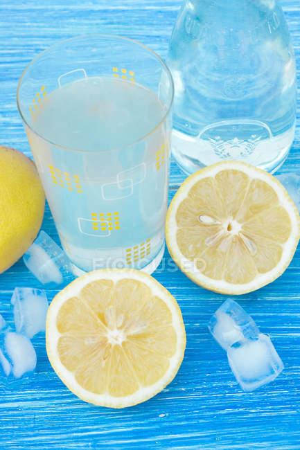 Glass of homemade Lemonade on blue wooden table with fresh lemons — Stock Photo