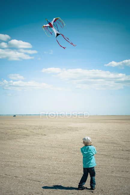 Дания, Ромо, Мальчик, летающий воздушным змеем в Северном море — стоковое фото