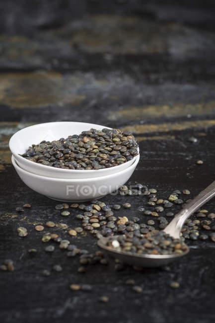 Lentilhas da Suábia em tigela branca pequena e colher na superfície escura, close-up — Fotografia de Stock