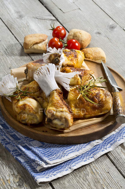 Chicken drums on wooden chopping board over towel — Stock Photo