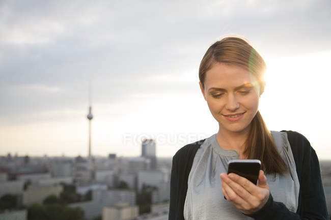 Young woman on rooftop terrace, using mobile phone — Stock Photo