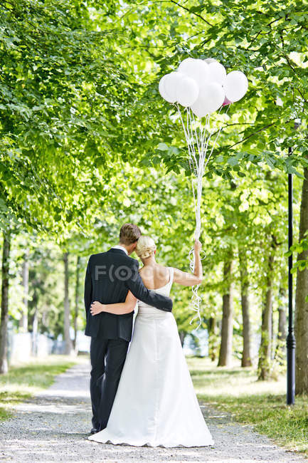 Alemanha, Bavaria, Tegernsee, casal de noivos andando sob árvores, segurando balões — Fotografia de Stock