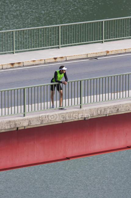 Германия, Бавария, мужской бегун, отдыхая после обучения на мосту — стоковое фото