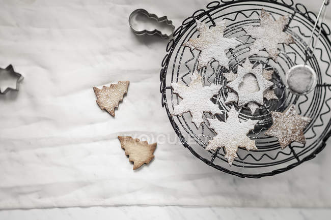 With powdered sugar sprinkled Christmas cookies, cake stand, strainer and cookie cutter on white ground — Stock Photo