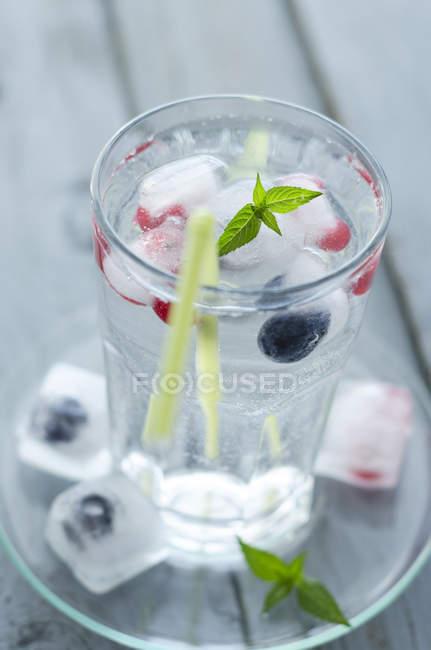Copo de água mineral com cubos de gelo e bagas congeladas — Fotografia de Stock