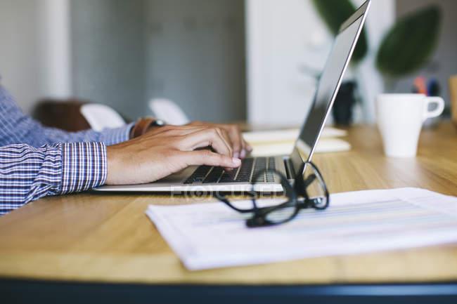 Close-up de mãos masculinas usando laptop no escritório — Fotografia de Stock