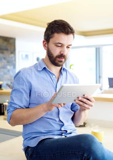 Uomo che lavora in cucina con tablet digitale — Foto stock