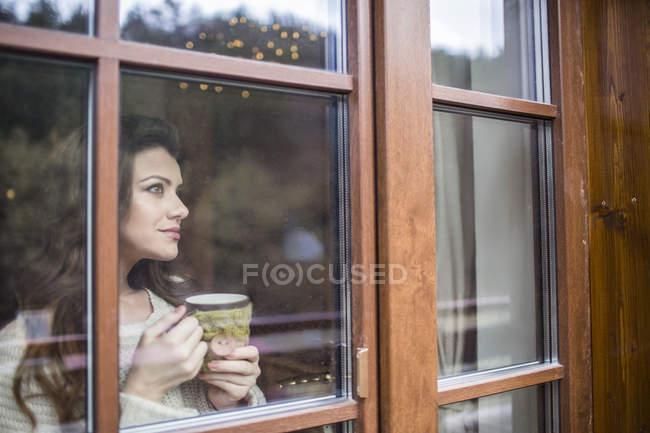 Giovane donna alla finestra con una tazza di caffè — Foto stock