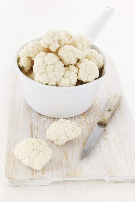 Cauliflower florets in bowl and on wooden chopping board with knife — Stock Photo