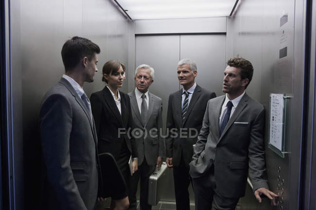 Group of caucasian businesspeople discussing in elevator — Stock Photo