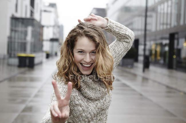 Portrait de jeune femme heureuse montrant signe de victoire — Photo de stock
