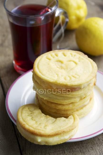 Lemon cookies with cup rose hip tea and lemons on wood — Stock Photo
