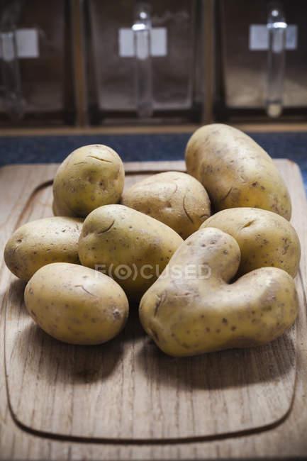 Rohe Kartoffeln auf Holzbrett — Stockfoto