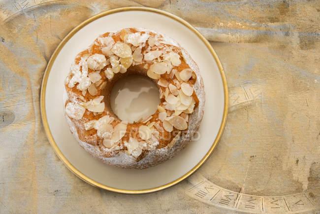 Almond ring cake on platter on shabby fabric — Stock Photo
