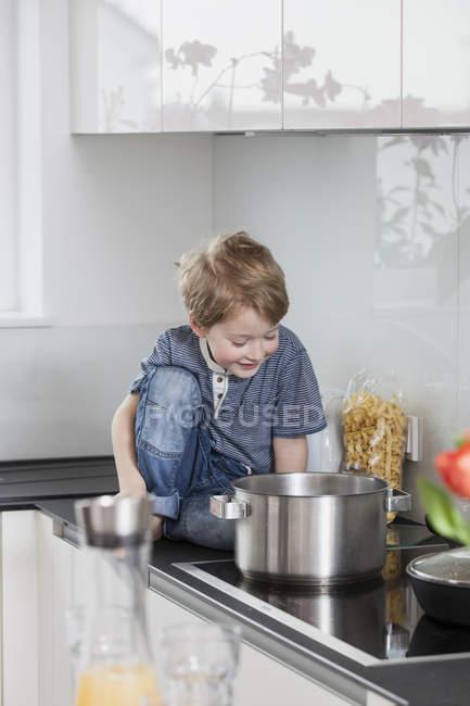 Garotinho, ajudando a preparar a comida na cozinha — Fotografia de Stock