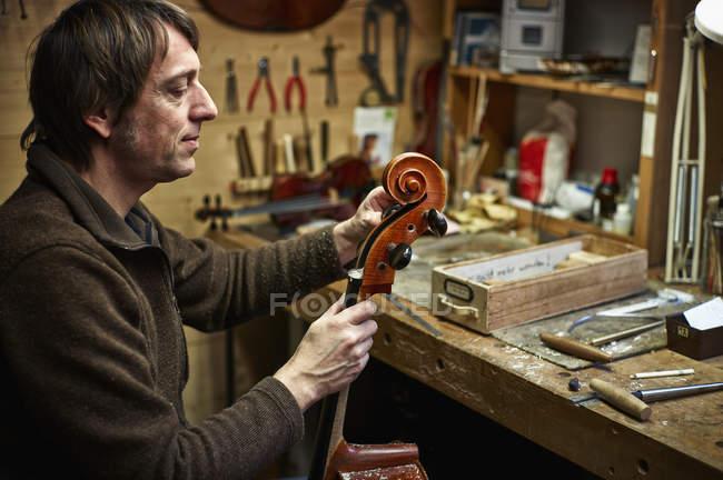 Geigenbauer justiert in Werkstatt einen Cello-Mechanismus — Stockfoto