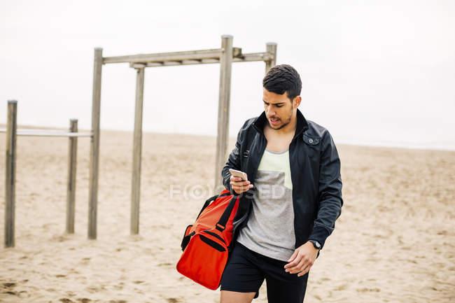 Junger sportlicher Mann mit Handy am Sandstrand — Stockfoto