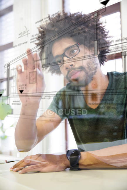 Young man using transparent touchscreen display — Stock Photo