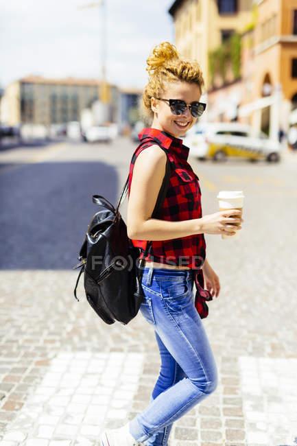 Italien, verona, lächelnde frau mit coffee to go in der stadt — Stockfoto