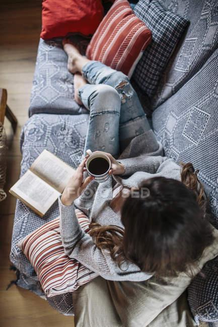 Jeune femme à la maison se détendre avec une tasse de café et d'un livre — Photo de stock