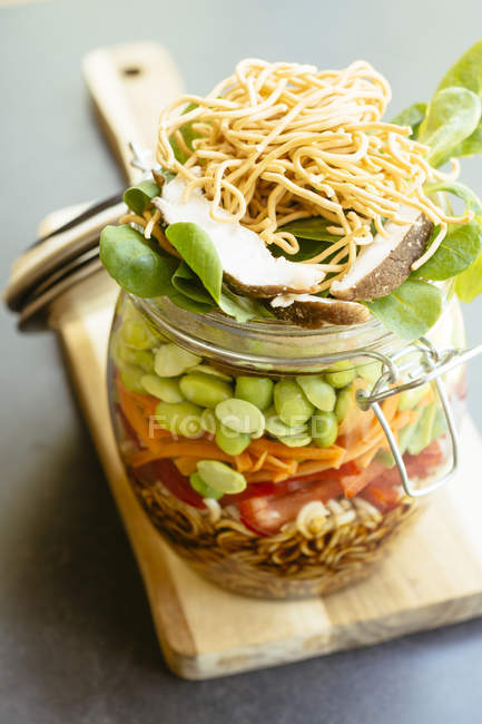 Asian salad in a jar with ramen noodles, red pepper, snow pea pods, carrots, edamame, shiitake mushrooms, salad greens, fried chow mien noodles and dressing — Stock Photo
