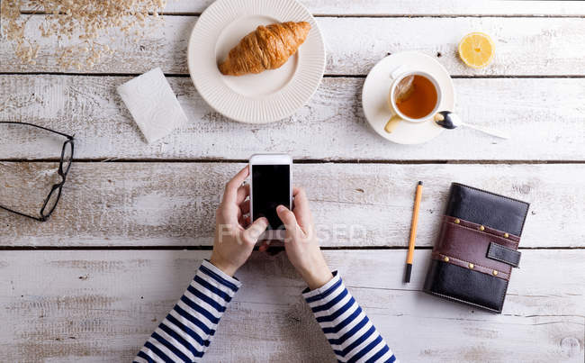 Man working smart phone and personal organizer while having breakfast — Stock Photo