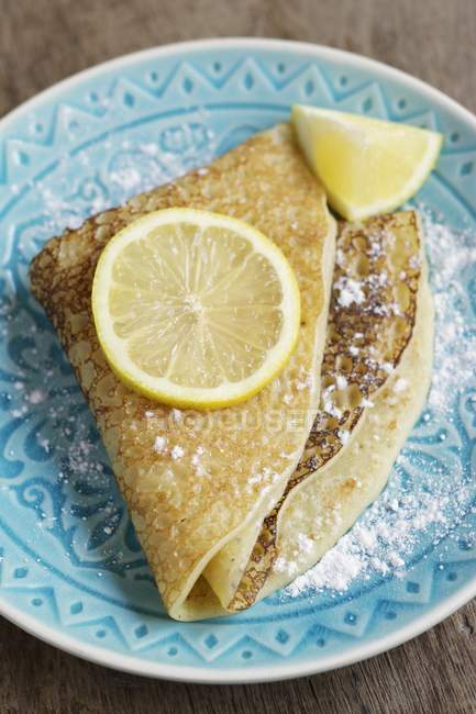 Sugar powdered pancakes with lemon on blue plate — Stock Photo