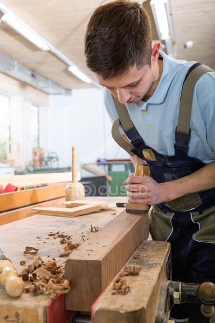 Карпентер стругання деревини в майстерні — стокове фото