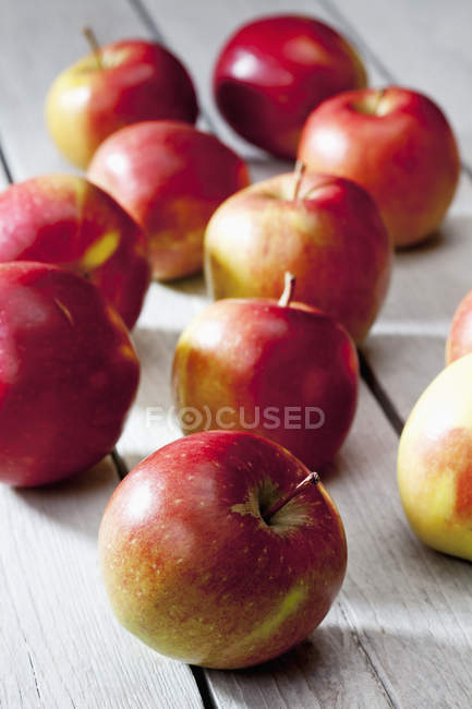 Fresh ripe apples on grey wooden table — Stock Photo